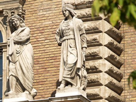 Two women. Sculpture on the wall. Budapest. Hungary.