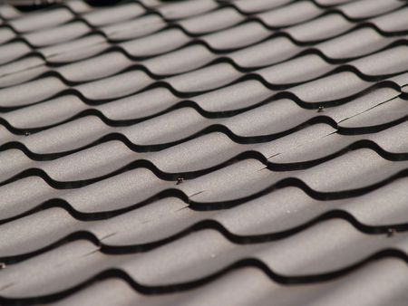Dark brown roof. Tile. Light and shade