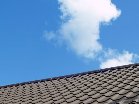 Dark brown roof. Blue sky background with clouds.