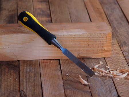 Chisel on the wood. Wooden planking background. Stock Photo