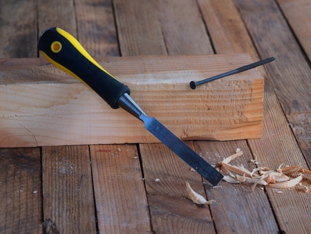 Chisel on the wood. Wooden planking background.