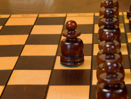 Black piece on the chess-board. One pawn before ohter pawns.