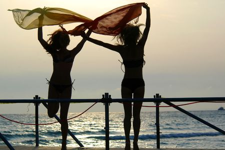 silhouettes of two young girls with scarfs dancing on a brige at sunset photo