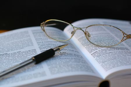 close up of glasses and pen on book page Stock Photo