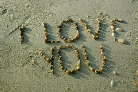 anniversary beach: &quot,I love you&quot, from seashells on sand beach