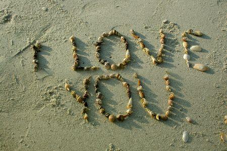 """carta de amor: """"Te quiero"""", de conchas marinas en playa de arena  Foto de archivo"""