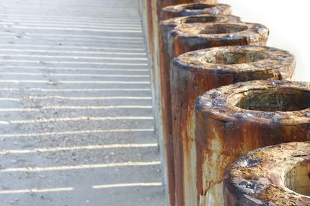 rusty tubes, partly isolated over white, shallow DOF photo