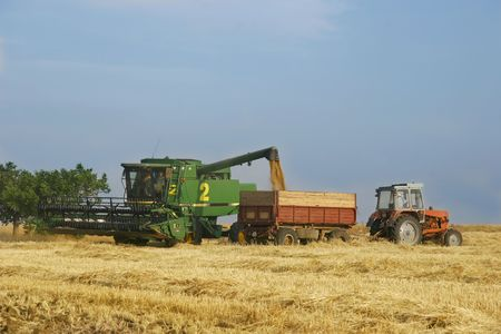 deere: combine and tractor on harvest wheat field Stock Photo