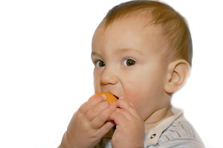 kiddie:  boy eating orange, isolated over white