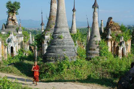 stupas: young monk walkng between stupas