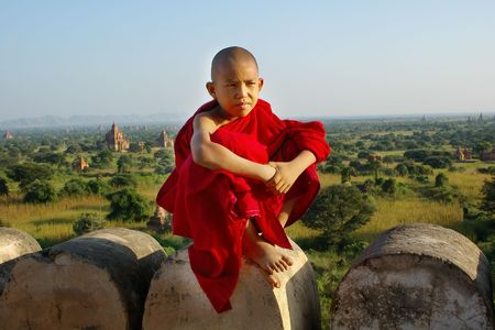 Myanmar: jeune moine bouddhiste sur le temple de fond