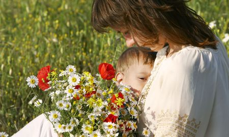 breastfeeding: mother feeding  in flowers Stock Photo