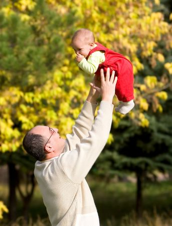 father playing with son in autumn park photo