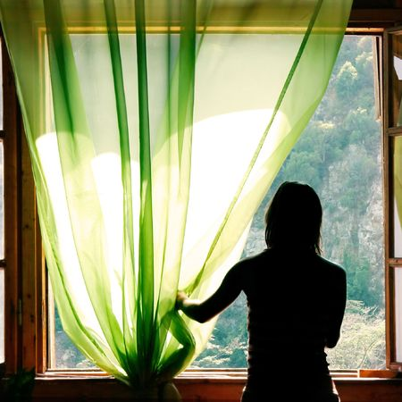 open girl: female silhouette at open window in old hotel Stock Photo