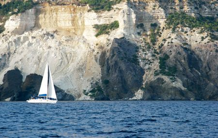 impregnable: small yacht on mountain background Stock Photo