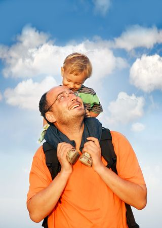 foster parenting: father and son on sky background