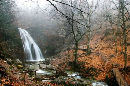 waterfall in foggy autumn forest photo