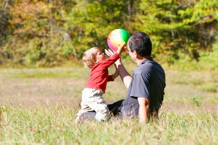 foster parenting: father playing with son outdoors Stock Photo