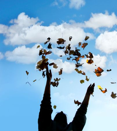 autmn: silhouette of man throwing up autmn leaves over sky