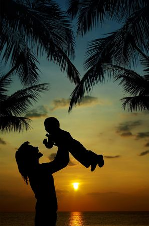 silhouette of mother and son at sunset in tropics photo