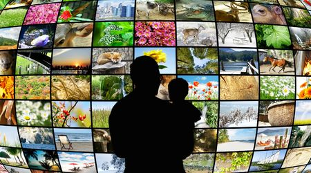 father and son looking at tv screens showing beauty in nature Stock Photo