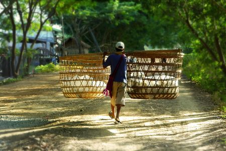 boy with bamboo buskets walking by road