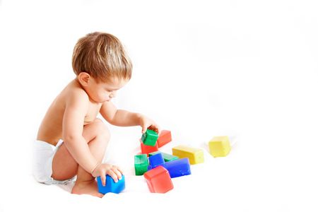 pampers: toddler playing with cubes over white