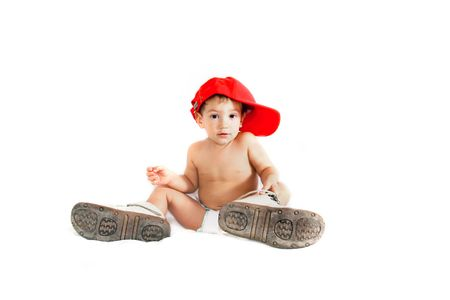 big foot: toddler boy in parents boots over white Stock Photo