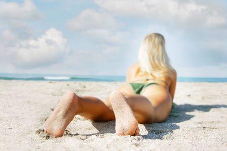 young girl on sand beach, focus on feet photo