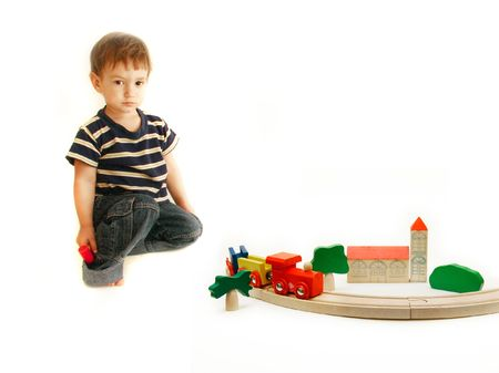 foster parenting: toddler playing with wooden train over white Stock Photo