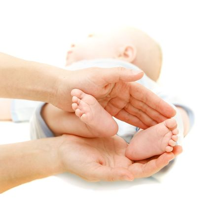 babys feet in parents hands over white photo