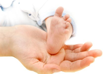 babys foot on parents hand photo