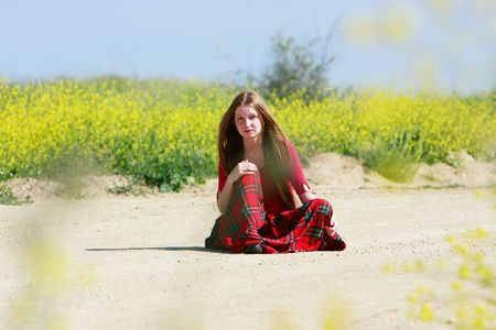 sad girl with long hair sitting on country road Stock Photo - 4890315