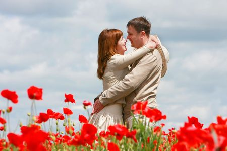 young loving couple on red poppies field