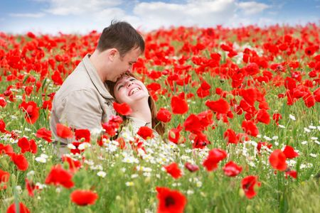 young loving couple on red poppies field photo