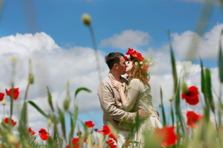 young loving couple on red poppies field Stock Photo - 4916763