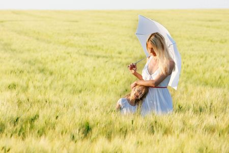 loving mother and daughter under white umbrella in green field Stock Photo - 4963221