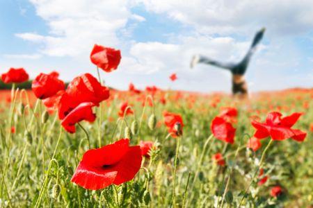 jumping girl in poppy field, focus on poppy photo