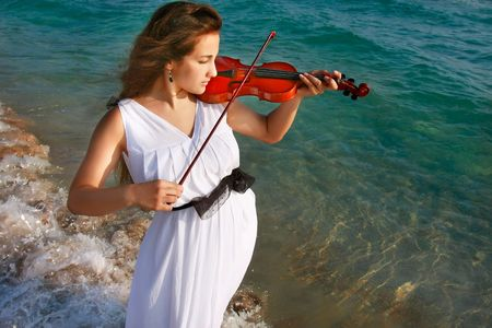 beautiful girl playing violin on sea background photo