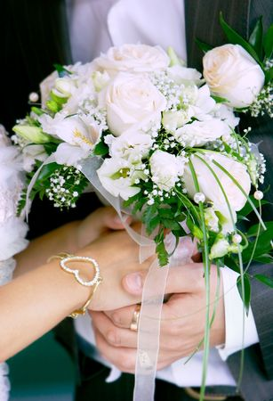 close up of brides and grooms hands with wedding bouquet photo