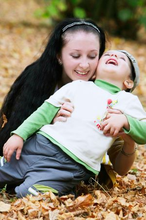 happy mother and son in autumn park photo