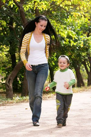 mother and son running in autumn park photo
