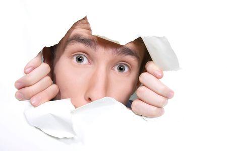 giovane uomo peeping attraverso il foro sulla carta
