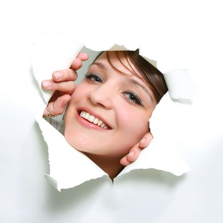 smiling girl peeping through hole in paper Stock Photo