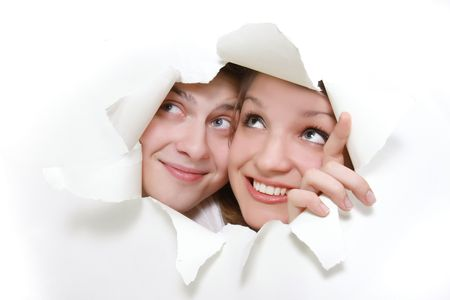 young couple peeping through hole in white paper