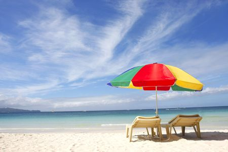 stoelen en kleurrijke paraplu op zand strand  Stockfoto