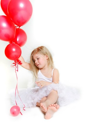 studio shot of little girl with red balloons photo