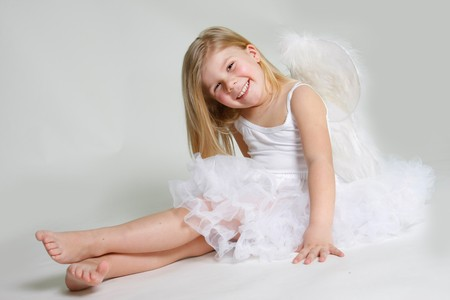 studio shot of little smiling angel girl photo