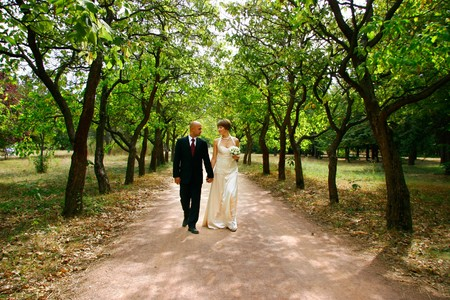 young couple walking in park on their wedding day photo