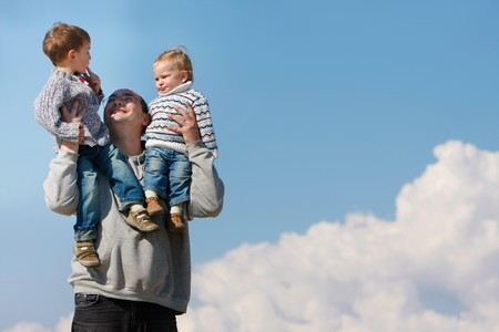 father holding two children on his shoulders over sky background photo